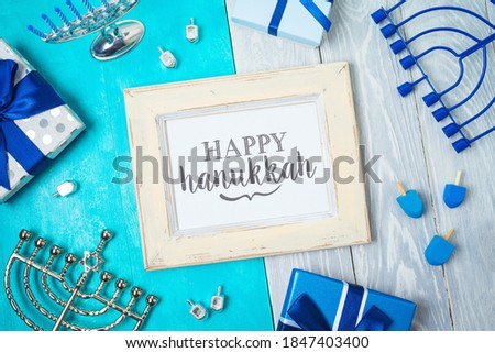 Jewish holiday Hanukkah greeting card with photo frame, menorah, gift box and spinning top on wooden table