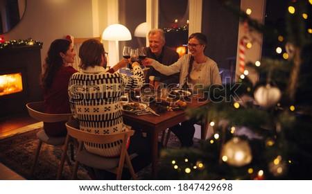 Family having a Christmas eve dinner together. European family toasting wine and enjoying dinner on Christmas eve. #1847429698