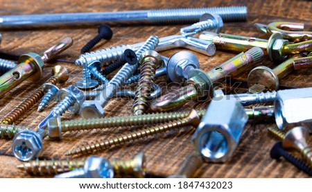 Nuts, screws, nuts, flat washers on a wooden background. Royalty-Free Stock Photo #1847432023