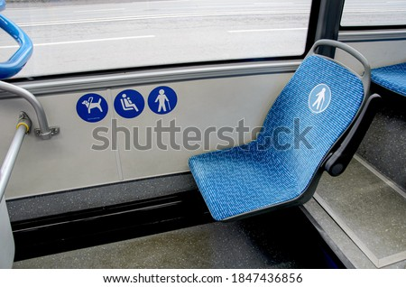 Blue fabric seat in the bus for elderly, people with disabilities and passengers with children. Space for guide dog in bus. Special seats in public transport for certain categories of passengers.