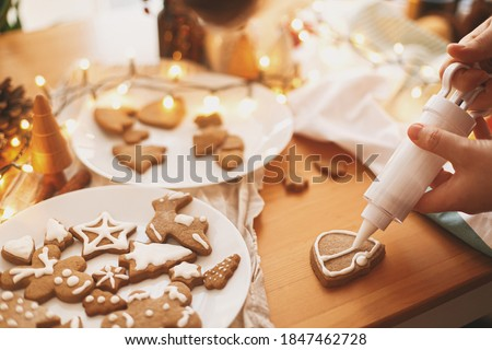Decorating gingerbread cookies with icing on rustic table with lights. Christmas holiday tradition and advent. Hands decorating baked christmas cookies with sugar frosting. Family time #1847462728