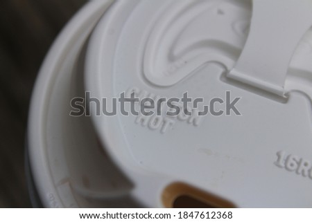 A coffee cup lid against a dark wooden background on a cold morning. The lid has a caution hot warning. Royalty-Free Stock Photo #1847612368