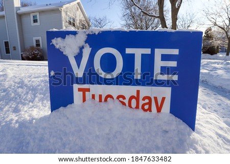"Vote sign ""Vote Tuesday"" covered in snow in a front yard"