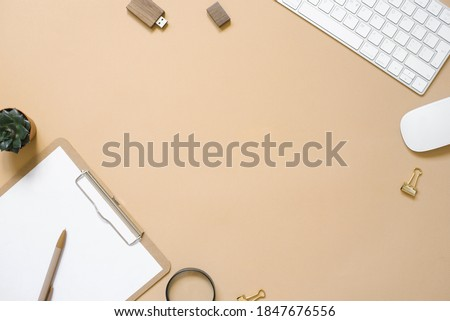 A tablet with a clean sheet of paper is on a beige background, a table with a computer and supplies. Top view and copy space