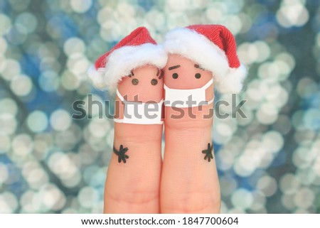 Fingers art of couple in medical mask from COVID-2019 celebrates Christmas. Concept of people in New Year hats. Toned image. Royalty-Free Stock Photo #1847700604