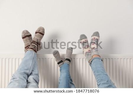 Family warming legs on heating radiator near white wall, closeup Royalty-Free Stock Photo #1847718076