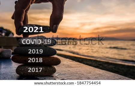 New Year 2021 is coming concept. Covid year 2020 to 2021 background. Positive turn of old year. Happy new year 2021 replace corona. New hopes, excitement with 2021. Man adding stone to pebble tower #1847754454