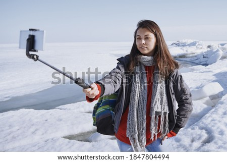 Female traveler outdoors at icy landscape using monopod to make selfie picture