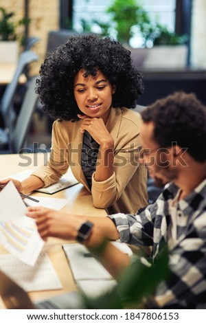 Two young diverse coworkers analyzing sales report while working together in the office Royalty-Free Stock Photo #1847806153