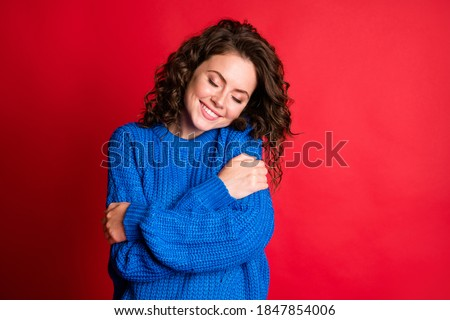 Photo of cute pretty dreamy lady curly hairstyle beaming white smile cuddle herself eyes closed fantasize wear blue knitted sweater pullover isolated red color background #1847854006
