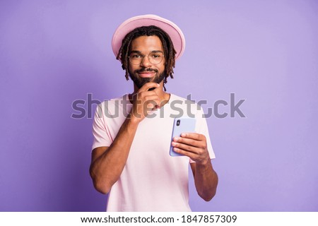 Photo portrait of thinking man in pink headwear holding phone in one hand touching chin isolated on vivid purple colored background