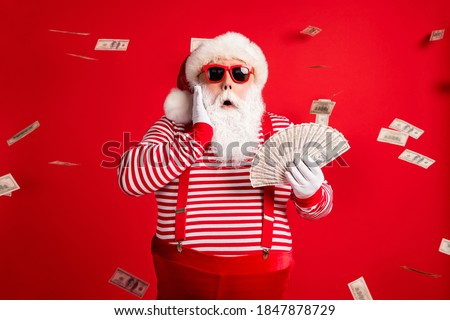 Photo of retired old man grey beard hold cash fan hand cheek shock money wear santa x-mas costume suspenders sunglass gloves striped shirt cap isolated red color background #1847878729