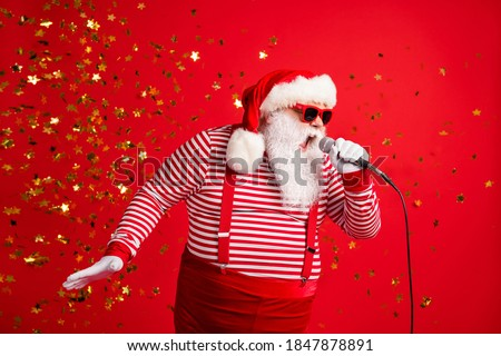 Photo of grandpa grey beard hold mic open mouth scream sing song karaoke wear santa claus x-mas costume suspenders sunglass striped shirt cap isolated red color background #1847878891