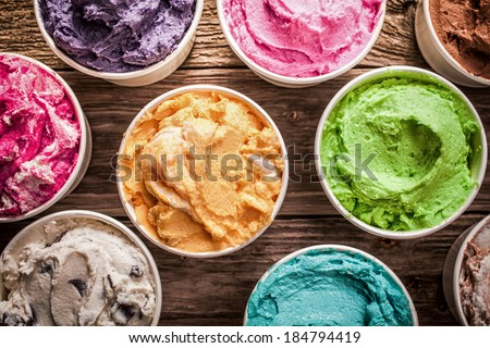 Array of different flavored colorful ice cream in plastic tubs displayed on an old wooden table at an ice cream parlor for delicious frozen snacks on a hot summer day Royalty-Free Stock Photo #184794419