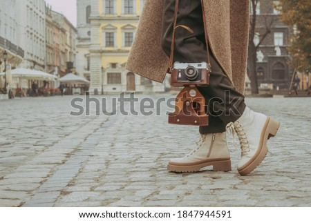 Faceless image of young stylish woman - travel blogger walking down the central city street using old-fashioned vintage camera. Autumn or spring outdoor fashion details, trendy street outfit