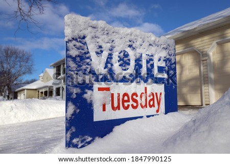 "Generic vote sign ""Vote Tuesday"" covered in snow in a front yard"