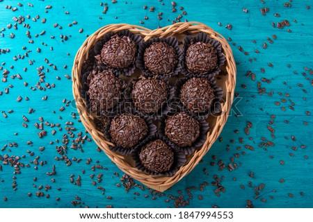 Brigadeiro.Traditional brazilian sweet chocolate in heart shaped basket Royalty-Free Stock Photo #1847994553