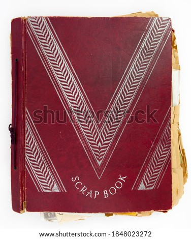Vintage red cover scrapbook with yellowed frayed pages. Royalty-Free Stock Photo #1848023272