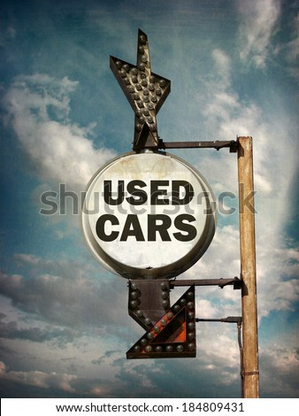 aged and worn vintage photo of used cars sign with arrow