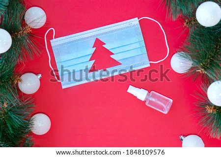 Medical protective mask with cut-out silhouette of Christmas tree and sanitizer on red background.With Christmas tree branches near the mask. Christmas and Happy New Year concept, coronavirus concept