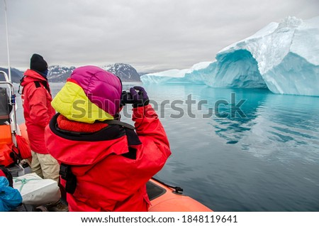 Tourist taking pictures of an iceberg from a dingy