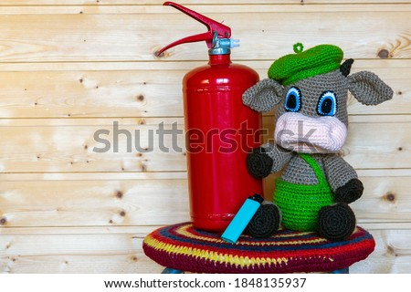 Handmade amigurumi doll goby with a fire extinguisher. Background from the board.