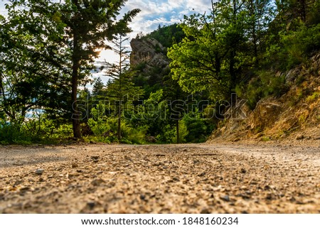 A picturesque low-angle view of a hiking path/rural road in the French Alps mountains on a sunny summer evening (Puget-Theniers, Alpes-Maritimes, Provence, France) Royalty-Free Stock Photo #1848160234