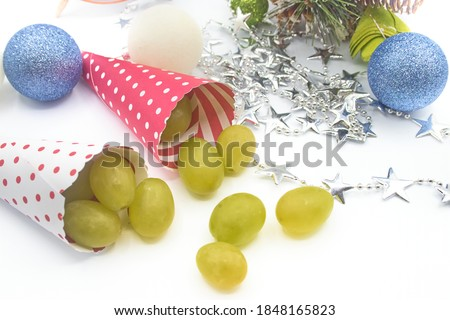 Cones with grapes to celebrate the end of the year with Christmas balls and a garland of stars.