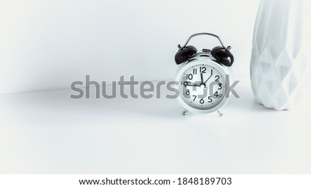 Image of alarm clock hands face watch timer on the wooden desk, with ceramic vase. Deadline concept, wake up in the morning. Copy space.