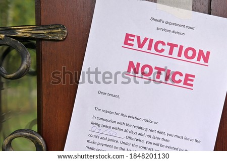 the notice of eviction of tenants hangs on the door of the house, front view Royalty-Free Stock Photo #1848201130