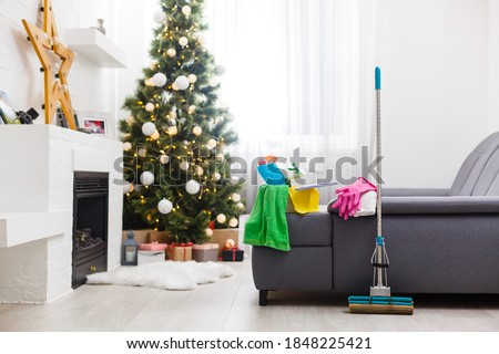 Cleaning before Christmas. Multicolored cleaning supplies. Sponges, rags and spray with festive decorations against modern home background #1848225421