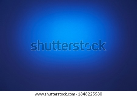 On a dark blue background, a blue oval cloud of light Royalty-Free Stock Photo #1848225580