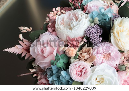 Beautiful flower arrangement in a white box. Flower shop concept. Floristics preserved flowers. White rose, mixed roses flowers, peony, blue hydrangea and eucalyptus. Royalty-Free Stock Photo #1848229009