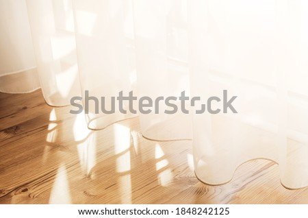 Transparent white curtain tulle from an open window. Sunny day, the sun's rays sunlight penetrate the room. Royalty-Free Stock Photo #1848242125