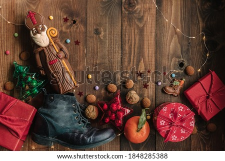Holiday background Saint Nicholas, Sinterklaas, with child's shoe, chocolate, cookies, nut, tangerines, gifts and sweets #1848285388