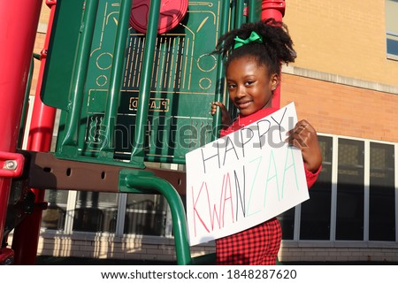 Child holding Sign words Happy Kwanzaa on holiday themed playground