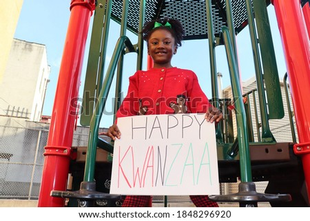 Pretty little girl holding happy Kwanzaa sign outdoors on playground