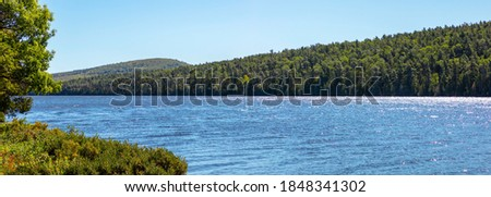 Upper Michigan lakeshore showing beautiful pictured rock beaches and bright green pines. The blue water sparkles on this summer day.