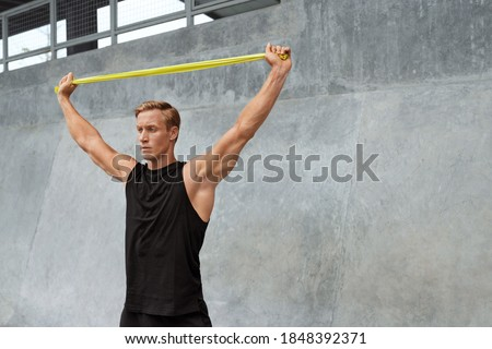 Young Man Stretching With Resistance Band Against Concrete Wall Outdoors. Handsome Caucasian Sportsman With Strong Muscular Body In Fashion Sportswear Doing Stretch Workout. Royalty-Free Stock Photo #1848392371
