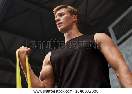 Young Man Stretching With Resistance Band Against Concrete Wall Outdoors. Handsome Caucasian Sportsman With Strong Muscular Body In Fashion Sportswear Doing Stretch Workout. Royalty-Free Stock Photo #1848392380