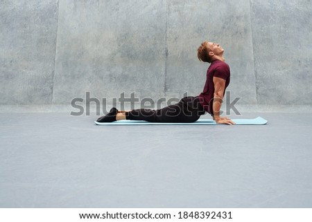 Young Man Stretching On Yoga Mat Against Concrete Wall Outdoors. Handsome Caucasian Sportsman With Strong Muscular Body In Fashion Sportswear Warming Up Before Intense Workout. Royalty-Free Stock Photo #1848392431