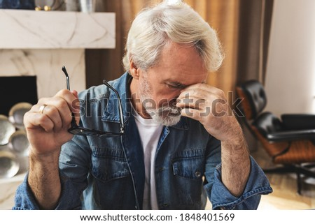 Tired men feel pain, eye strain holds glasses, rubbing dry irritated eyes, fatigue from working at a computer, stressed man suffers from headaches, poor eyesight, vision problems Royalty-Free Stock Photo #1848401569