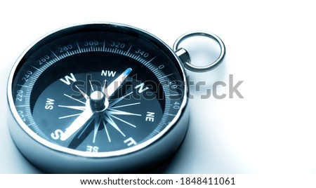 Classic magnetic compass, metal navigational compass on a white background.