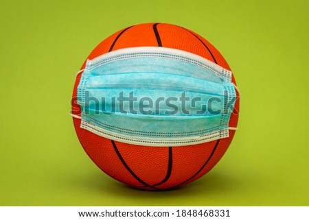 Basketball ball wearing surgical medical face mask. Concept for Coronavirus COVID 19 pandemic and epidemic affecting basketball seasons game suspend.
