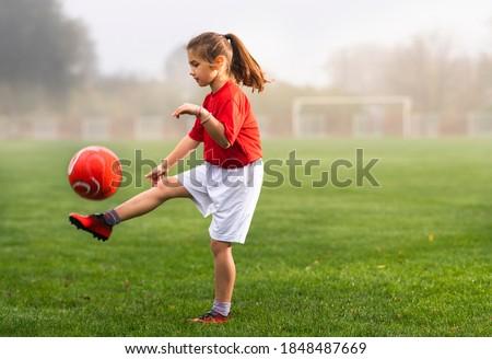 Girl kicks a soccer ball on a soccer field Royalty-Free Stock Photo #1848487669