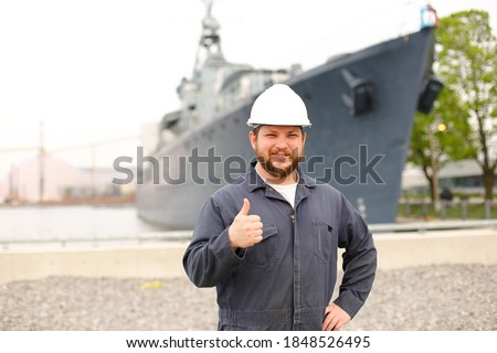 Portrait of marine captain standing near big vessel in background, showing thumbs up and wearing helmet with work jumpsuit. Concept of maritime job and profession, marine team. Royalty-Free Stock Photo #1848526495