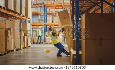 Shot of a Warehouse Worker Has Work Related Accident. He is Falling Down BeforeTrying to Pick Up Heavy Cardboard Box from the Shelf. Hard Injury at Work. Royalty-Free Stock Photo #1848610903