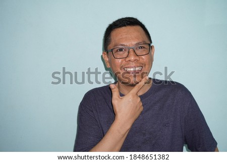 Happy and funny expression of Indonesian young man stock photo on green bright background. self potrait.