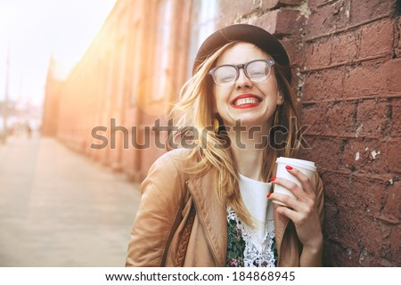 Cheerful woman in the street drinking morning coffee in sunshine light #184868945