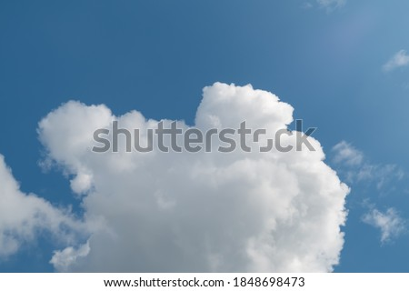 Low angle view of fluffy cumulus clouds against blue sky background. Royalty-Free Stock Photo #1848698473